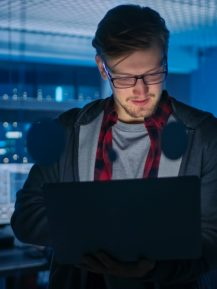 Portrait of a Smart Focused Young Man Wearing Glasses Holds Laptop. In the Background Technical Department Office with Specialists Working and Functional Data Server Racks