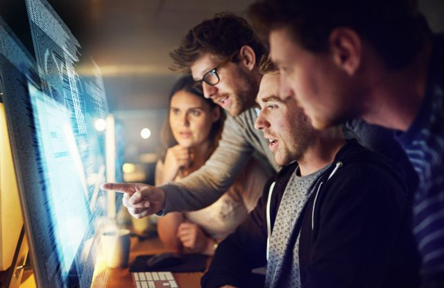 Shot of a group of programmers working on a computer code at night